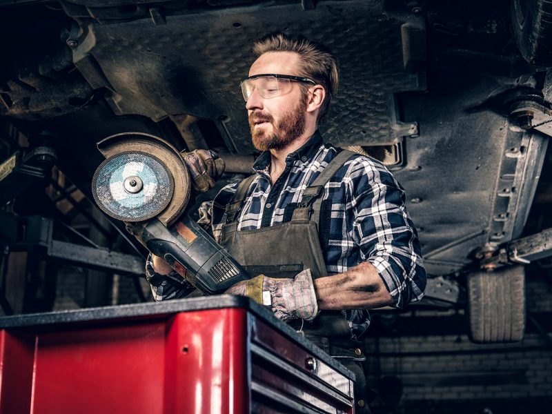mechanic-in-protective-googles-holds-angle-grinder-small